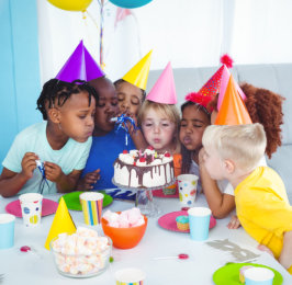 kids on a birthday party blowing candles