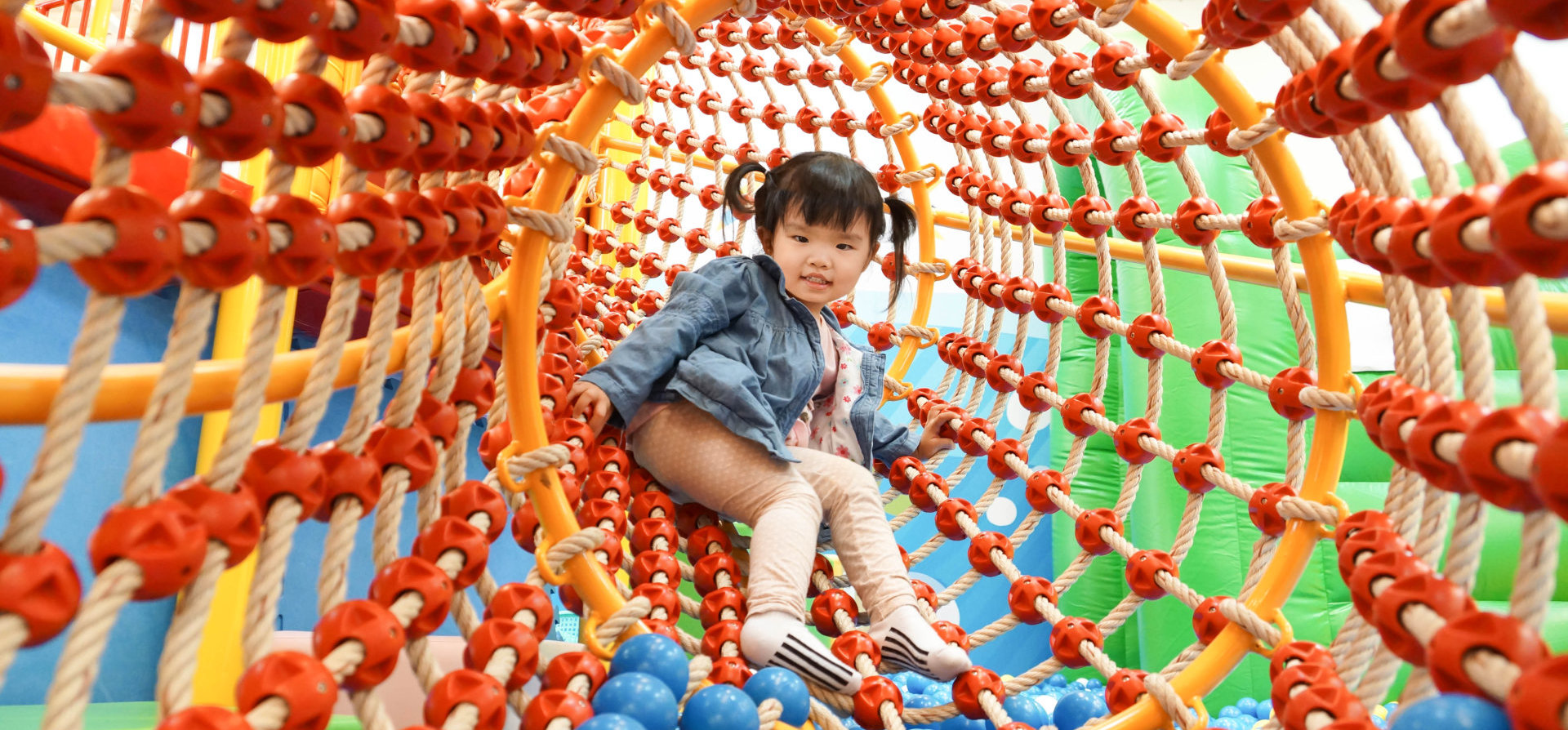 happy young girl inside a rope tunnel